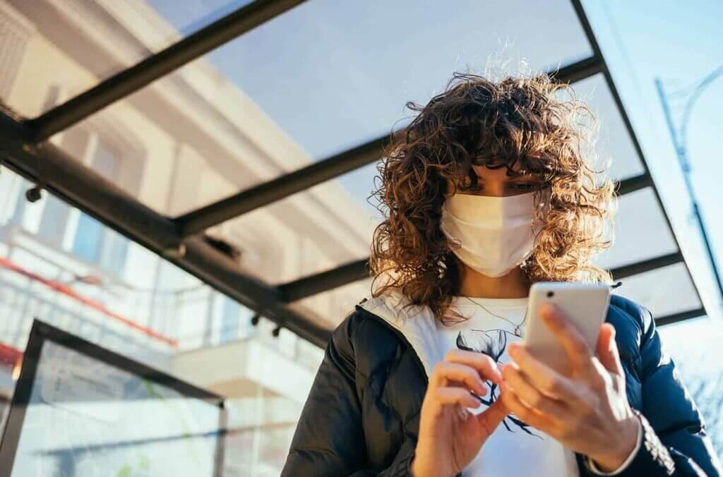 Frau mit Maske schaut auf Handy